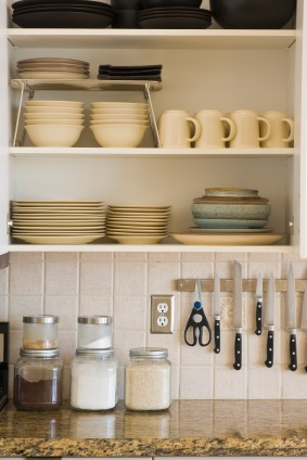Open cupboard with stacks of dishes, bowls and cups